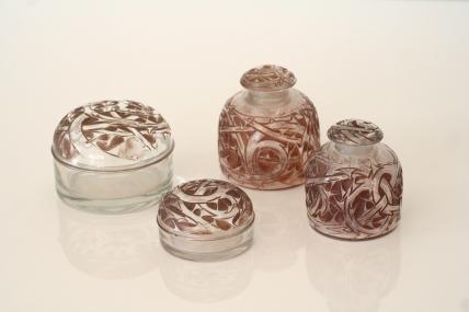 Ensemble de quatre flacons en verre, signés LALIQUE (1860-1945) - Garnitures de Toilette - Modèle Épines, créé en 1920
