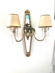 Paire d'appliques des Années 1950. La platine en forme de losange en bois laqué ivoire et doré à fond de miroir, supportant en son centre un bouquet de feuillage en métal laqué, d'où partent 2 branches, se terminant par des bobèches et cristaux. Etat : Abats jour d'origine, usure d'usage et quelques petits manques. Dimensions : Hauteur : 53 cm largeur : 38 cm Prix : 850€ --------------------------------------- Pair of sconces from the 1950s. The diamond-shaped plate in ivory and gilded lacquered wood with mirror background, supporting in its center a bouquet of lacquered metal foliage, from which 2 branches end with bobeches and crystals. Condition: Original lampshades, normal usage wear and some minor losses. Dimensions: Height : 53 cm width : 38 cm Price: 850 €